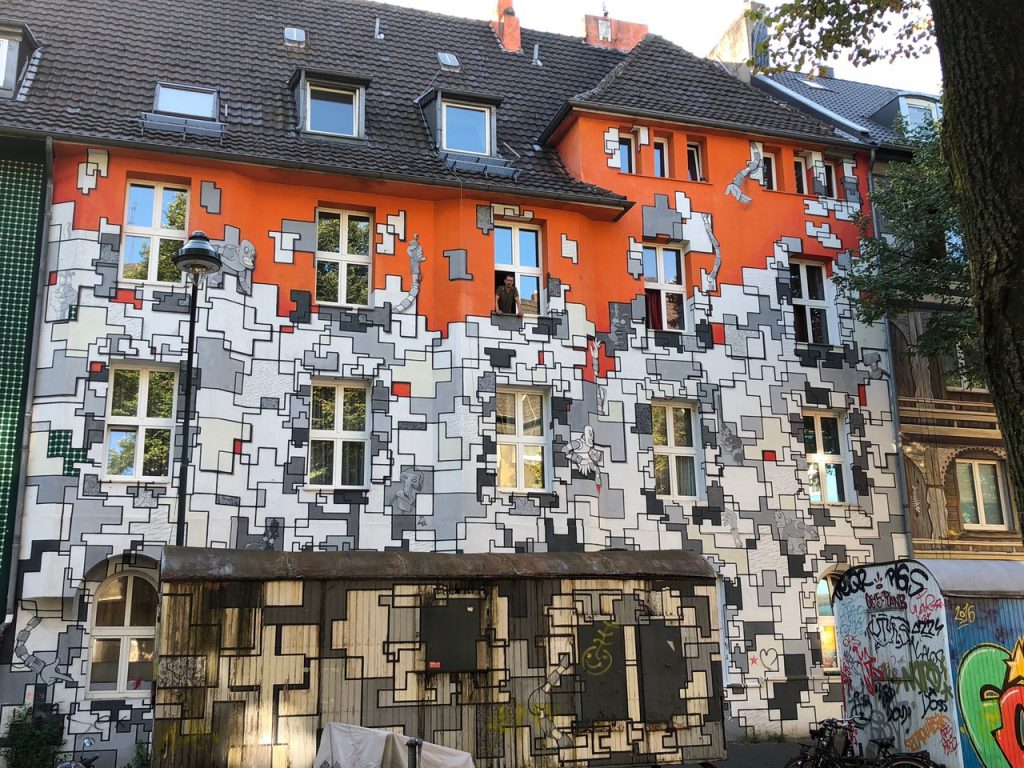 Apartment building entirely painted with a geometric pattern in grey and orange