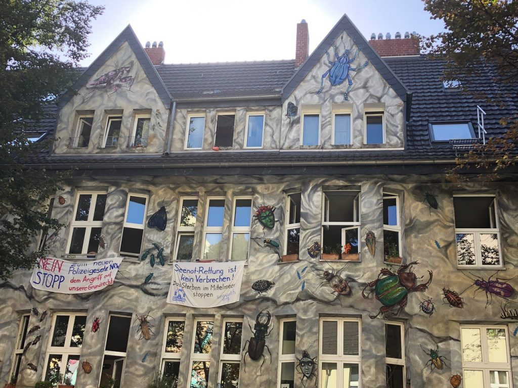 Grey building with insects painted onto it and banners hanging from the windows