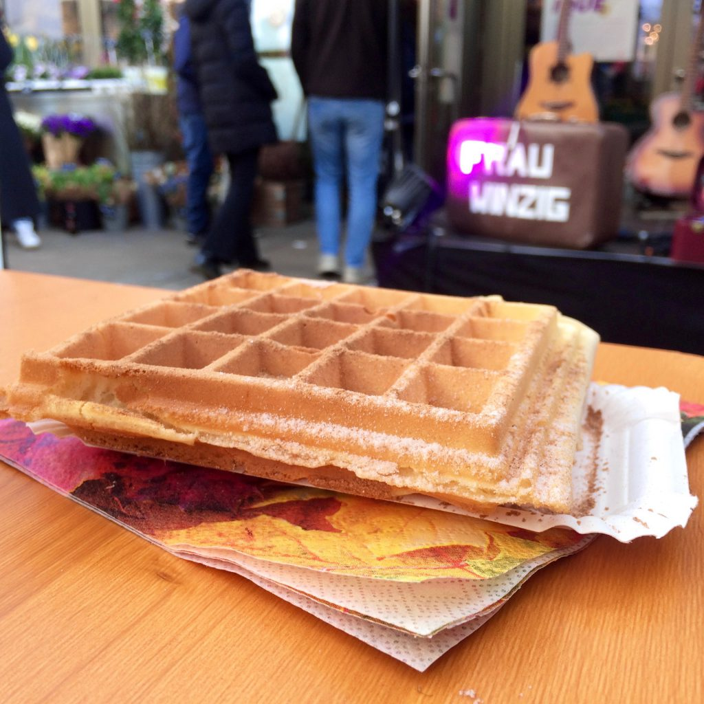 Waffle on a table at Markthalle, Cologne, with a stage behind