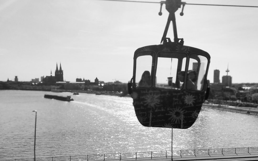 Monochrome cable car above the river Rhine with Cologne Cathedral in the background