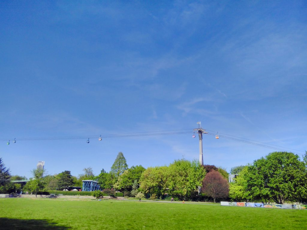 Sunny lawns, trees and a cable car crossing the picture