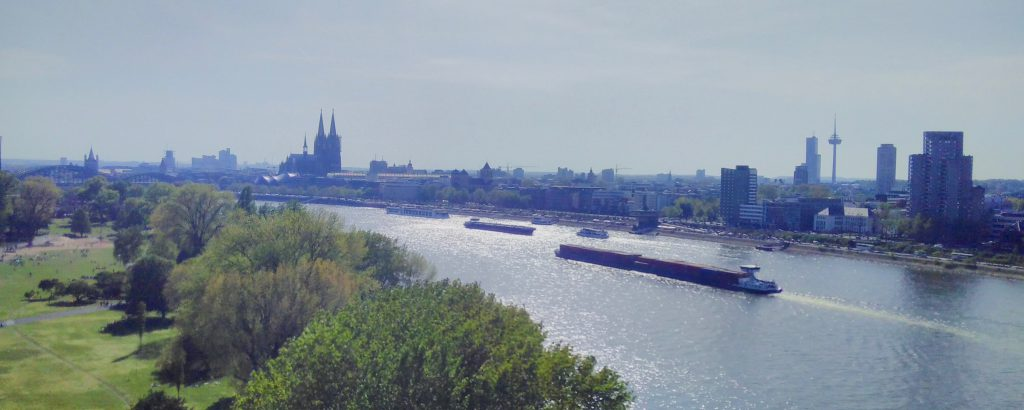 Skyline of Cologne with large cargo ships travelling up the Rhine