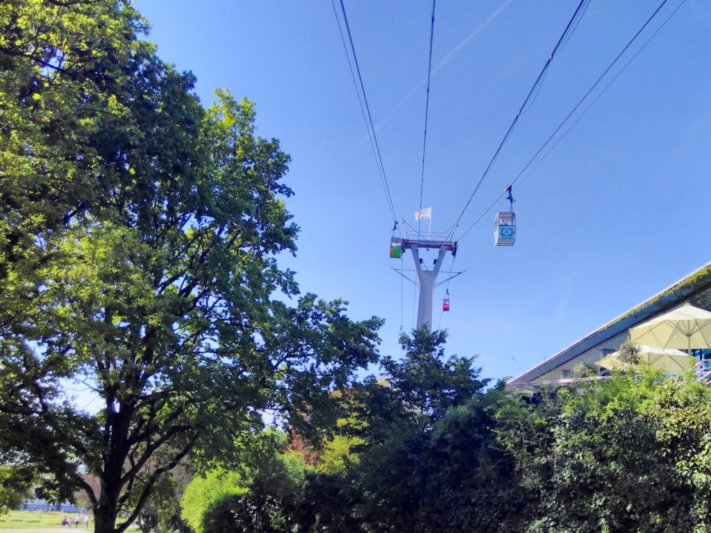 Cable cars going up into a blue sky over the trees of the Rheinpark