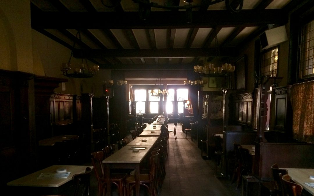 Traditional dark wood beer hall interior with a central long table, at Brauerei Paeffgen, Cologne