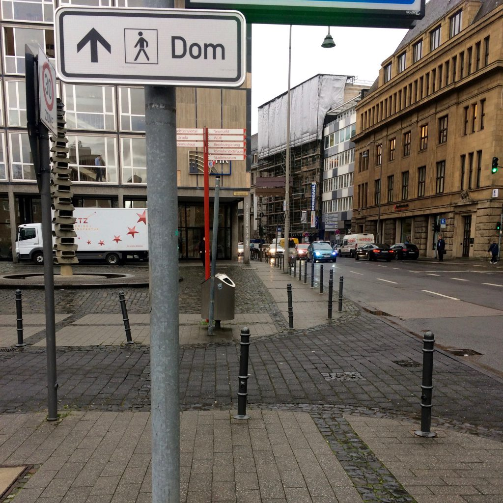 "White sign saying ""Dom"" points down Gereonstrasse in Cologne towards the Catherdral"