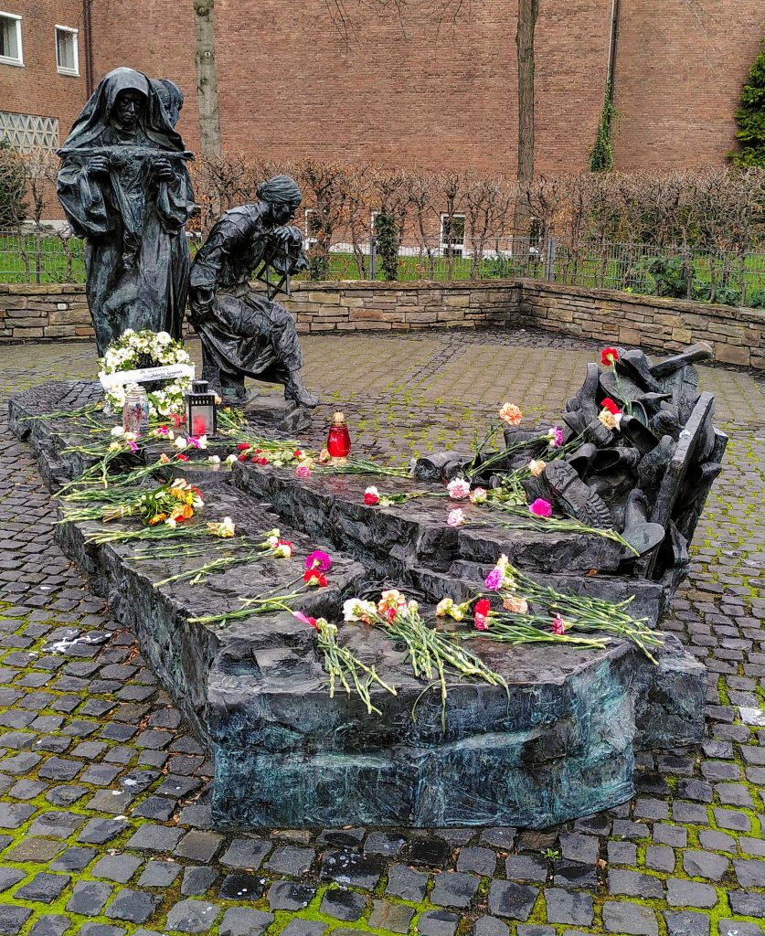 The Edith Stein Monument in Cologne covered in flowers