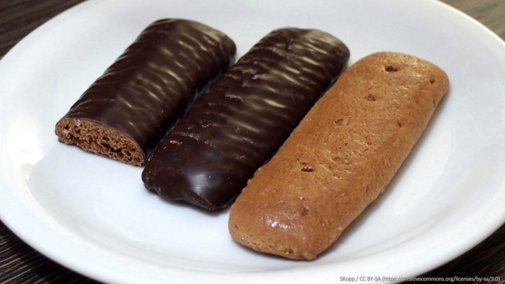 3 Aachner Printen cakes, two covered in chocolate on a white plate