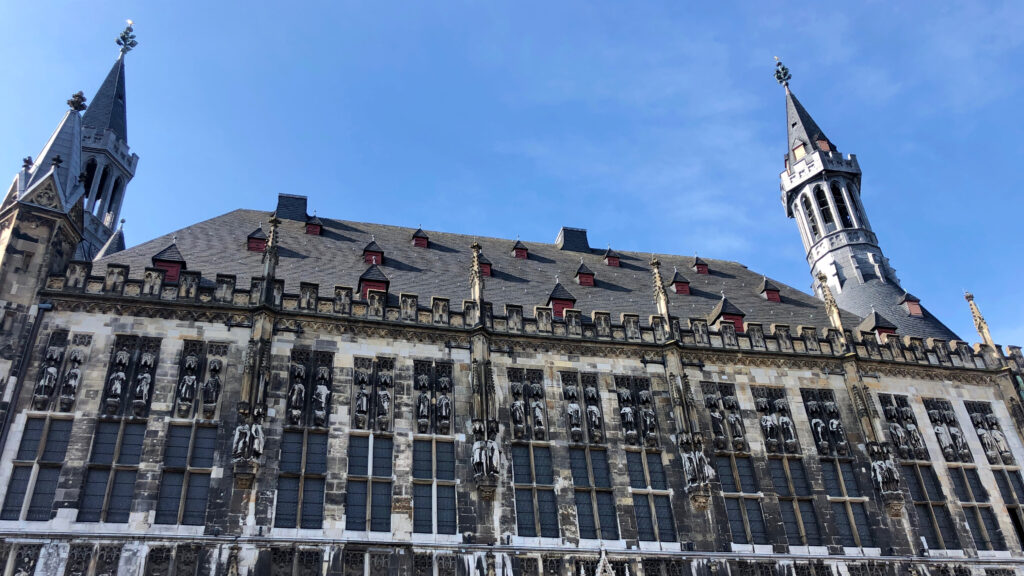 Aachen Town hall looking at the roof with statues and a blue sky