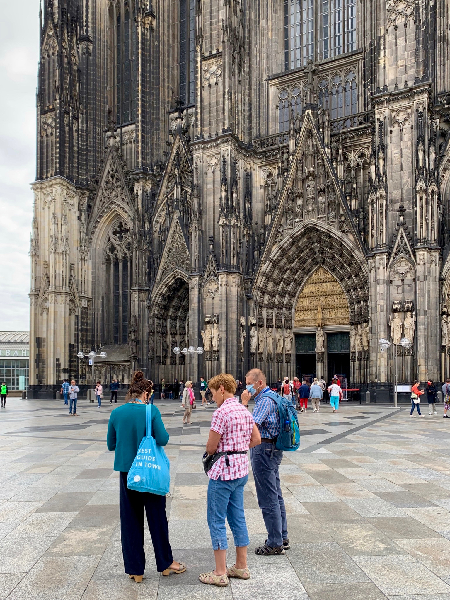 Two walking tour group members ask some questions of their guide outside the Cologne Cathedral