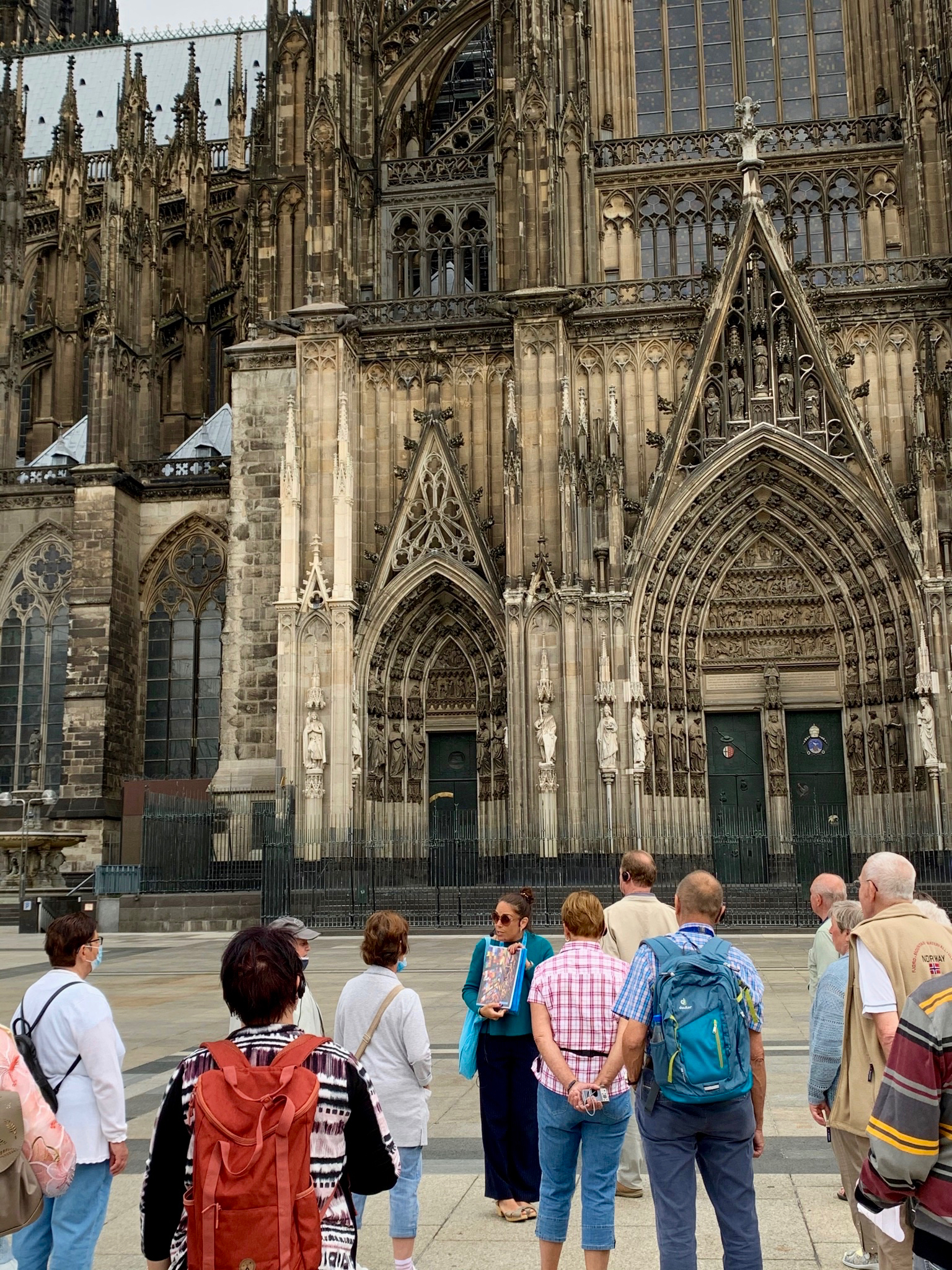 Walking tour group learning about the history of the Cologne Cathedral