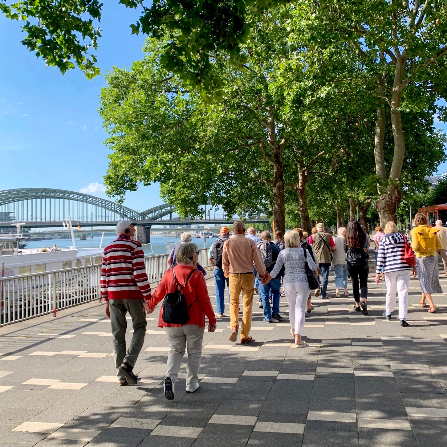 Tour group walks along the riverbank in Cologne